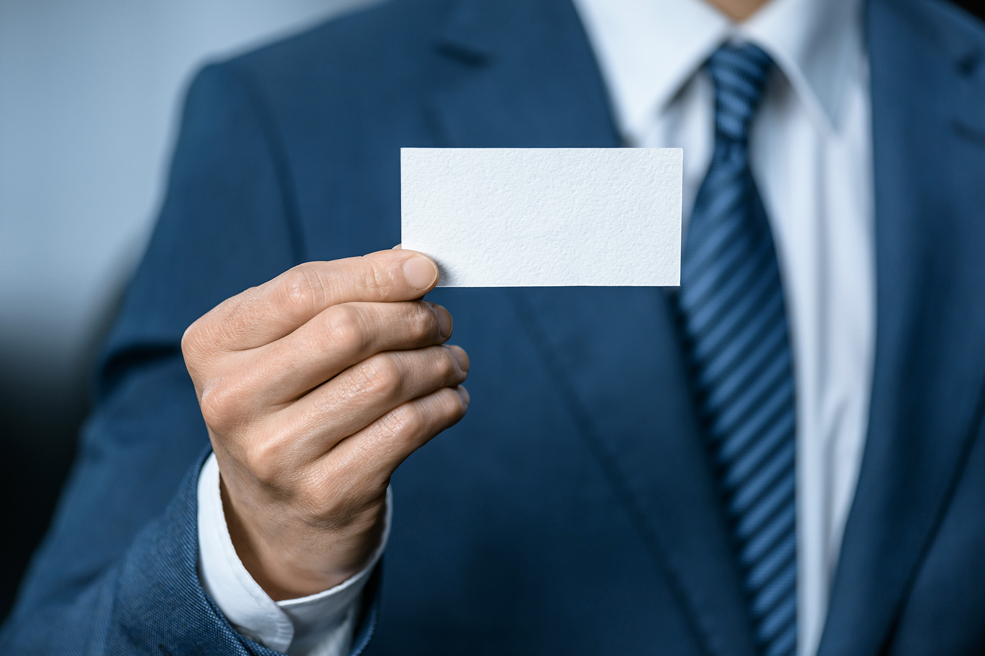 Man in business suit presenting blank business card